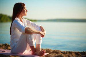 Progressive Muskelrelaxation nach Jacobson - Frau sitzt am Wasser
